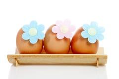 Drei Eier auf hölzerner Platte Stockbilder