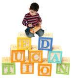 Drei Einjahresjunge, der auf Alphabet-Blöcken spielt Stockbild