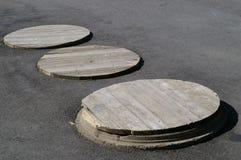 Drei Einsteigeloch-Abdeckungen stockbilder