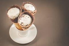 drei Eiscreme mit Kegel in der Schokolade auf a in einer weißen Eiscreme Schale/drei mit Kegel in der Schokolade auf a in einer w stockfotos