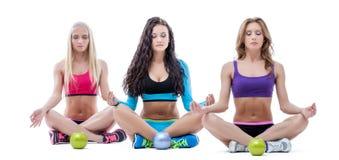 Drei entspannte Mädchen, die in Lotussitz meditieren Stockfotos