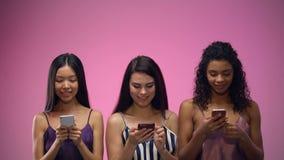 Drei entzückende gemischtrassige Frauen, die mobile Apps verwenden und oben, Schablone schauen stock video footage