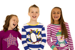 Drei entzückende Kinder, die tragende Weihnachtspyjamas lachen Lizenzfreie Stockfotos