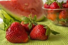 Drei Erdbeeren in Huelva auf einer grünen Tischdecke Lizenzfreie Stockbilder