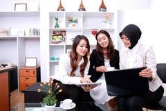 Drei erfolgreiche Geschäftsfrauen, die am Bürowohnzimmer sich treffen stockbilder