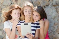 Drei erschraken jugendlich Freundinnen und Tablettencomputer Stockbilder