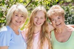 Drei Erzeugungen der Frauen Familie, die zusammen Zeit im Garten verbringt Lizenzfreie Stockfotos