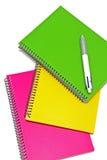 Drei färbten Notizbücher mit einem Stift auf weißem Hintergrund Stockfoto