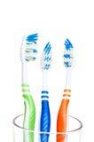 Drei färbten Zahnbürsten getrennt auf Weiß Stockbild