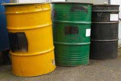 Drei Fässer in einer Reihe, in einem Gelb, in einem Grün und in einem Schwarzen stockfoto