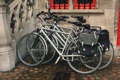 Drei Fahrräder, wenn die Aktenkoffer gegen die Wand geparkt sind lizenzfreies stockbild