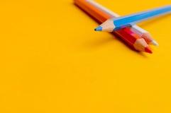 Drei farbige Bleistifte auf gelbem Hintergrund lizenzfreie stockfotos