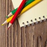 Drei farbige Bleistifte und Notizbuch auf Holztisch Lizenzfreies Stockfoto