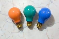 Drei farbige Glühlampen auf einem Marmorhintergrund Lizenzfreie Stockfotos
