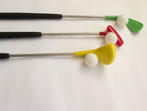 Drei farbige Golfclubs mit Bällen auf weißem Hintergrund stockbild