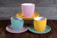 Drei farbige Tassen und Untertassen auf hölzernem Hintergrund Stockbild