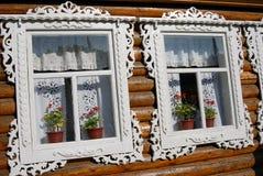 Drei Fenster eines hölzernen Grafschaftshauses verziert durch weiße Rahmen Stockfotos