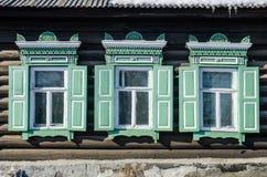 Drei Fenster mit dem hölzernen geschnitzten Architrav im alten Holzhaus in der alten russischen Stadt stockfotos