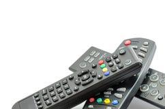 Drei Fernsehfernbedienungen über weißem Hintergrund Stockfotografie