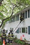Drei Feuerwehrmänner auf Brandort vor einem Gebäude Stockbilder