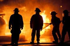 Drei Feuerwehrmänner in der Uniform ein Feuer kämpfend stockbild