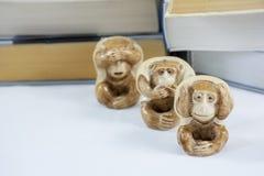Drei Figürchen Affe mit vielen Büchern Lizenzfreie Stockfotos