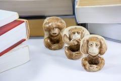 Drei Figürchen Affe mit vielen starken Büchern Lizenzfreie Stockfotos