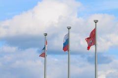 Drei Flaggen auf Pfosten und Himmel - Flagge von Russland, Flagge der Dauerwellestadt Stockbild