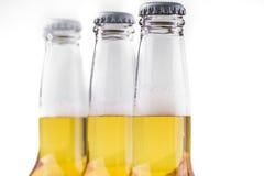 Drei Flaschen Bier getrennt auf Weiß Stockfotografie