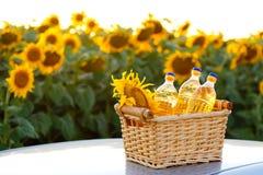 Drei Flaschen Sonnenblumenöl in einem Weidenkorb lizenzfreie stockbilder