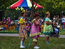 Drei Frauen in den Clownkostümen stehen auf grünem Gras im Park Stockfotos