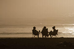 Drei Frauen, die auf Strandschattenbildern sitzen stockfoto
