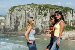 Drei Frauen, die chimarrão auf Torres-Strand nehmen lizenzfreie stockfotografie