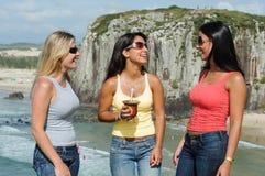 Drei Frauen, die chimarrão auf Torres-Strand nehmen stockfotografie