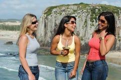 Drei Frauen, die chimarrão auf Torres-Strand nehmen stockfotos