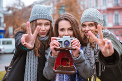 Drei Frauen, die draußen Foto auf Kamera machen Stockbild