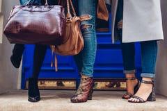 Drei Frauen, die draußen stilvolle Schuhe und Zubehör tragen Schönheitsmodekonzept Damen, die weibliche Handtaschen halten stockfoto