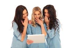 Drei Frauen, die einen Tablettenauflagencomputer verwenden, werden entsetzt Lizenzfreies Stockfoto