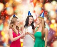 Drei Frauen, die Hüte mit Champagnergläsern tragen lizenzfreie stockfotografie