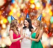Drei Frauen, die Hüte mit Champagnergläsern tragen stockbilder