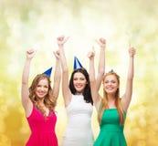 Drei Frauen, die Hüte tragen und sich Daumen zeigen lizenzfreie stockfotos