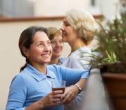 Drei Frauen, die Tee am Balkon trinken Stockfoto