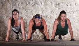 Drei Frauen drücken Ups in Matte-Lager-Training stockfotos