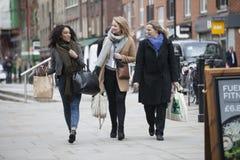 Drei Frauen gehen mit Taschen hinunter die Straße und besprechen sich Stockfotos