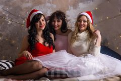 Drei Frauen im Sankt-Hutlächeln sitzt einen Raum nahe von Weihnachten d Lizenzfreie Stockfotografie