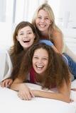 Drei Frauen im spielenden und lächelnden Wohnzimmer Stockbild