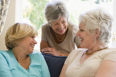 Drei Frauen im Wohnzimmer sprechend und lächelnd Lizenzfreies Stockfoto
