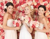 Drei Frauen mit dem Hintergrund voll von den Rosen Stockfoto