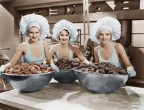 Drei Frauen mit enormen Schüsseln Schaumgummiringen Stockfotografie