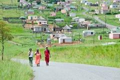 Drei Frauen mit Mandela-Häusern im Hintergrund von Zulu Village, Zululand, Südafrika Lizenzfreies Stockfoto